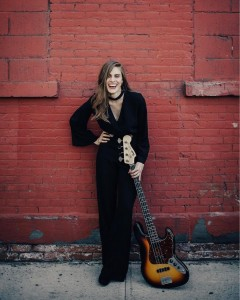 Jazz guitarist Lucy Jane Clifford stands against a red wall with her guitar.